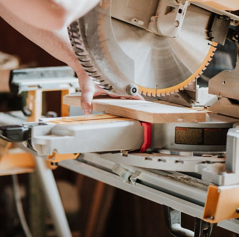 work shop with saw cutting wood for a custom sized photo framing